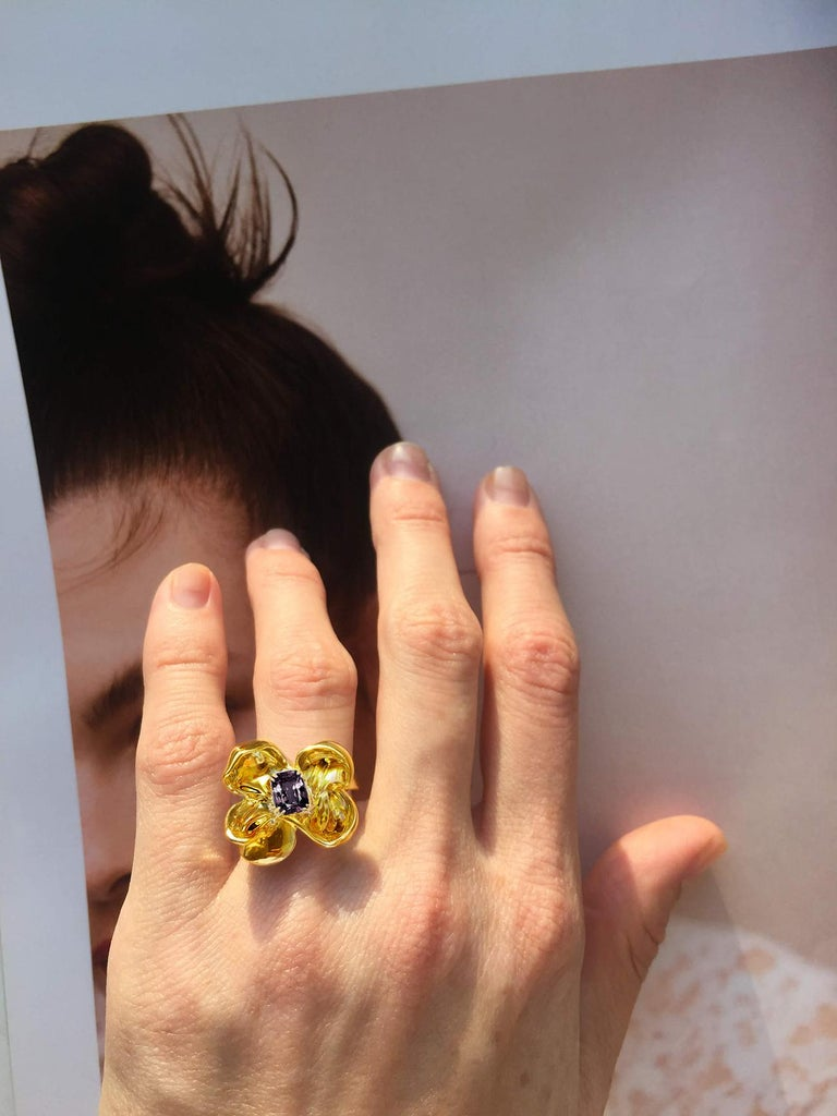 This Magnolia Flower contemporary cocktail ring is in 18 karat yellow gold with storm purple cushion spinel (1.34 Ct). The water-surface of the spinel multiplies the light, mirroring on the golden petals. The weight of the ring is aprox. 8.5