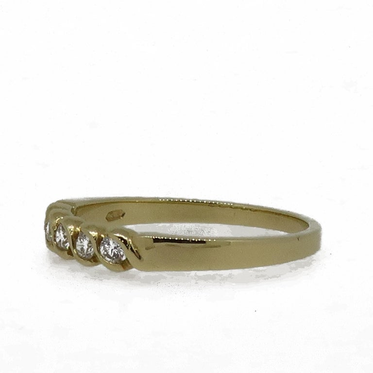 18 Karat Yellow Gold Diamond Eternity Band Ring  A delicate diamond eternity ring. Consisting of five white brilliant cut diamonds, weighing 0.16ct in total. The diamonds are set in a rub over S style setting. It would make the perfect wedding band