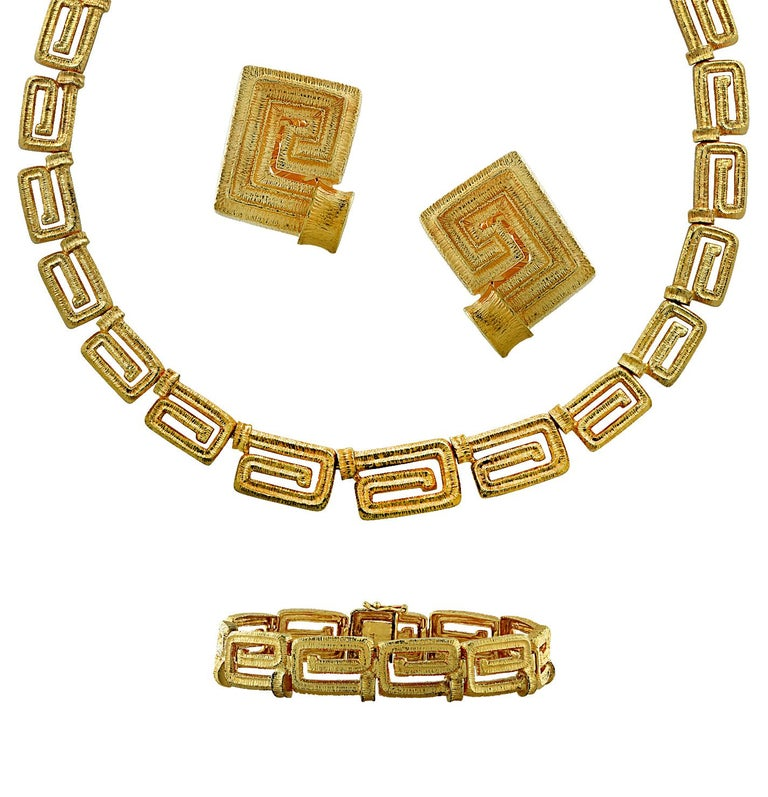 Stunning Greek Key jewelry suite featuring a necklace, bracelet and earrings crafted in 18 karat yellow gold. The necklace measures 17 inches in length and 11.8 mm in width. It closes with a hidden box clasp and safety lever. The bracelet measures