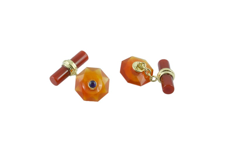 The front face of these exquisite cufflinks has a striking octagonal shape that is convex, multifaceted, and adorned in the center with a cabochon sapphire. Both the front face and the cylindrical toggle are in carnelian, with a post made of 18k