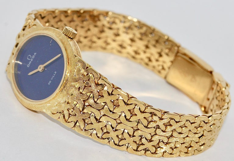 18 Karat Yellow gold ladies' watch, Omega De Ville, with lapis lazuli dial.  Mechanical manual wind movement.  Glass has small scratches on the glass.  Fully functional.  Including certificate of authenticity.