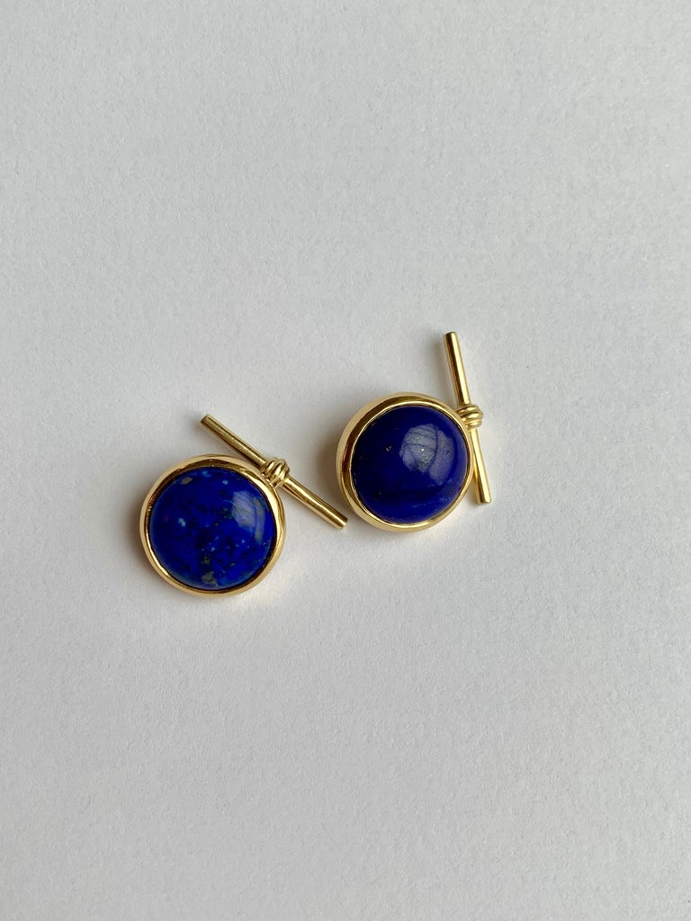 The striking blue shade of Lapis Lazuli is set off nicely with yellow gold mounting. These round cabochon cut cufflinks set in 18kt yellow gold with chain and gold T bar are a modern and sophisticated.  Dimensions: 16mm   A beautiful rich blue lapis