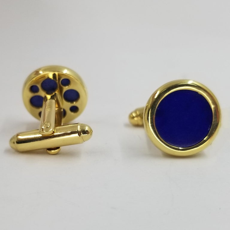 Set of 2 cufflinks crafted in 18 karat yellow gold (stamped). The fronts are polished bezels with flat circular Lapis Lazuli inlay. The backs are a hinged torpedo style for easy dressing.