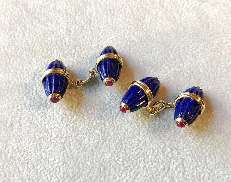 These striking cufflinks feature identical front face and toggle whose oval shapes evokes the silhouette of a barrel, carved with grooves that add dynamism to their texture. They are made of lapis lazuli, adorned with cabochon rubies at the edges.
