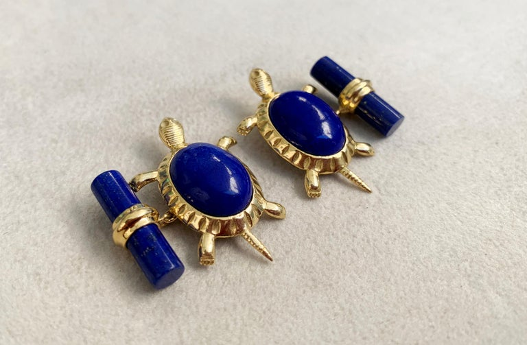 These unique cufflinks combine the deep blue of lapis lazuli with the warmth of 18 karat yellow gold.  The precious metal is used to make the post and mounting of the front face in the shape of the legs and tail of a turtle, while the cylindrical