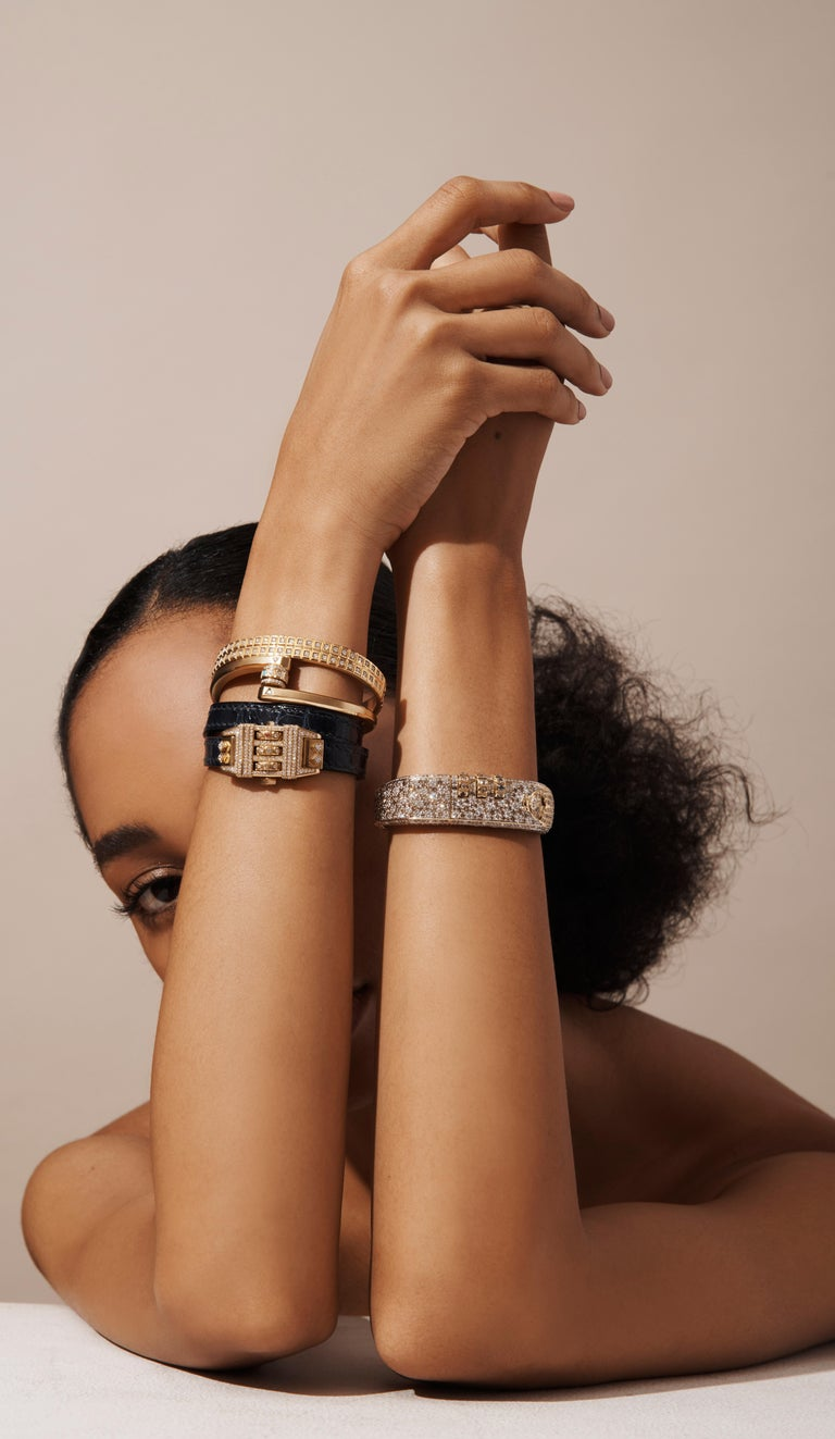 18 Karat Leather Wrap Code Bracelet features a solid 18k Yellow Gold clean polished face with black and white diamonds on the dial and a custom code that opens and locks the bracelet onto the wearer's wrist, and completed with a Double Wrap Black
