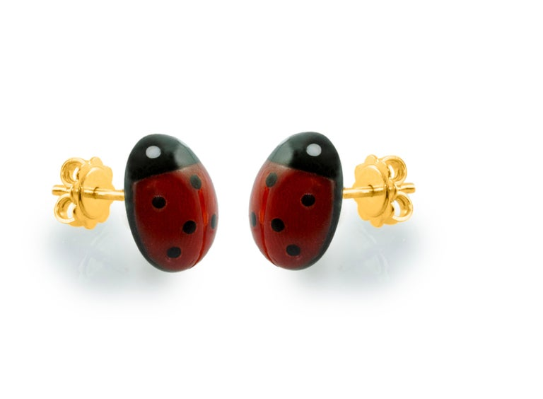 These stud earrings  are made with coral sourced in the Mediterranean and Onyx, each face have been hand-carved shaped like a ladybug with a smooth, bulging surface.  The post in the back is made of 18k yellow gold.