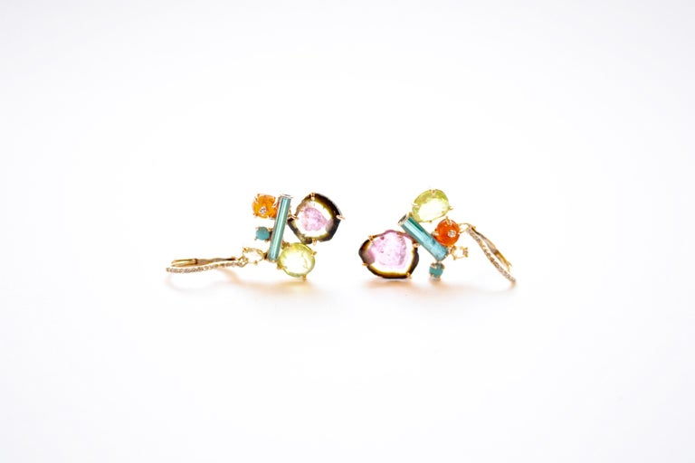 Penny Eardrops A pair of eighteen-karat yellow gold earrings set with a mélange of different colours and cuts of stones, including Mexican fire opal, tourmaline, turquoise, and chrysoberyl,  along with a dash of diamonds. Each cluster hangs off a