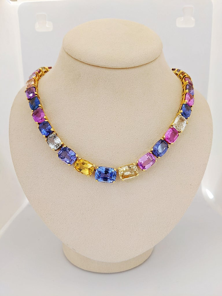 This show- stopping sapphire necklace is comprised of an array of natural colored sapphires including blues, yellow, pinks and purples, set in 18kt yellow gold. The brilliantly colored cushion cut sapphires graduate in size and lay elegantly on ones
