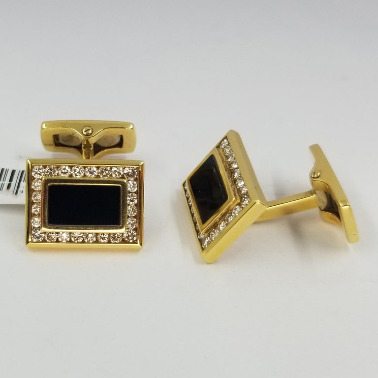 Set of 2 cufflinks crafted in 18 karat yellow gold (stamped 750), onyx, and channel set diamonds. 48 round diamonds of VS clarity & G color total approximately 1.00cttw. Hinged backs for easy dressing and removal.