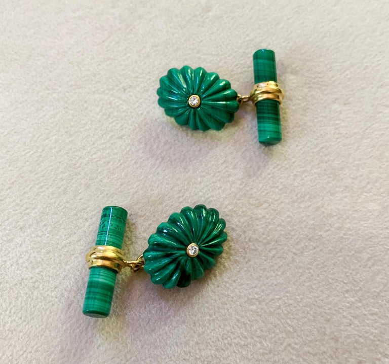 """Striking and bold, this pair of cufflinks is made entirely in malachite,  the toggle is a simple cylindrical bar, while the front face is shaped as a oval with the classic """"fesonato"""" texture, the center of each oval is decorated with a"""