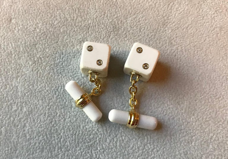 This sophisticated pair of cufflinks is entirely made of white agate and it features a simple, cylindrical toggle attached to the front with an 18k yellow gold post.  The front face is shaped as a cube with its striking white surface highlighted by