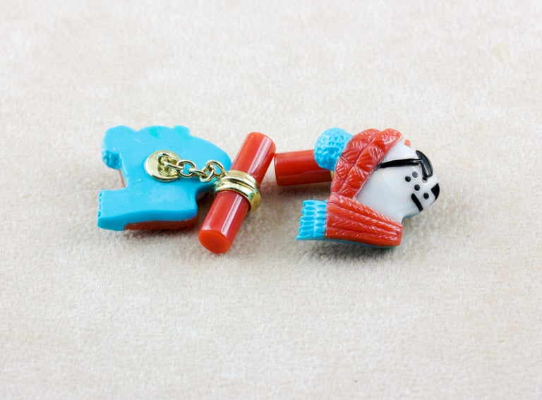 This playful pair of cufflinks depicts the profile of a polar bear portrayed as if dressed up for the winter with sunglasses, scarf, and hat. The animal is made of Mediterranean coral which is also used to make the cylindrical toggle, accents in