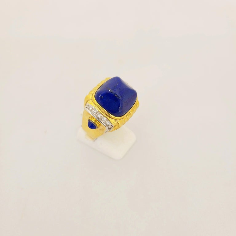 This 18karat yellow gold ring, by Cellini Jewelers NYC, is designed with a large Lapis Lazuli sugarloaf cabochon center. The ring is accented with 0.30 cts. of  round diamonds and 2 smaller lapis cabs. Stamped 750 Ring size 6.5 Sizing options are