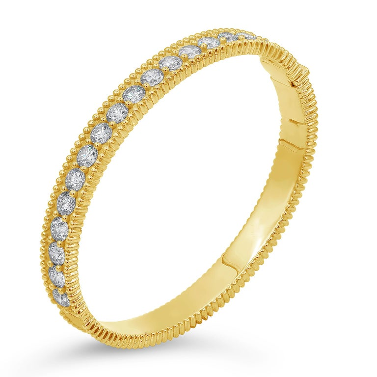 A brilliant and stylish bangle bracelet showcasing a row of round brilliant diamonds, set in shared prongs, all the way around the 18 karat yellow gold mounting. Finished with beaded edges. Diamonds weigh 5.68 carats total.  Style available in