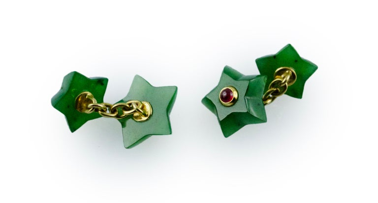 These charming cufflinks are shaped as stars repeated for both front face and toggle. Their whimsical silhouette is made of jade and adorned in the center with cabochon rubies. The mounting of the precious stone is in 18k yellow gold.  Dimensions: