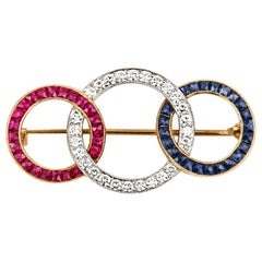 18 Karat Yellow Gold Ruby Diamond and Sapphire 'Tri-Ring' Brooch, circa 1950s