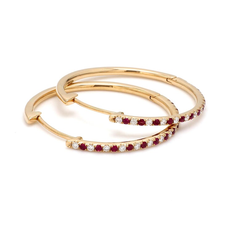 A Beautiful Handcrafted Hoop Earring in 18 karat Yellow Gold with Natural Brilliant Cut Colorless Diamond And  Vibrant Rubies. A Statement piece for Evening Wear  Natural Diamond Details Pieces : 26 Pieces Weight : 0.28 Carat  Clarity of Diamond :