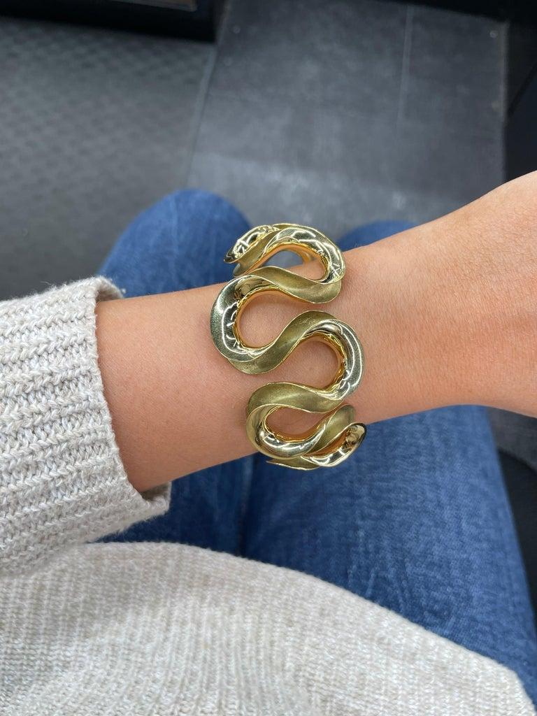 18 Karat yellow gold bangle cuff featuring a swirl motif weighing 47.6 grams.
