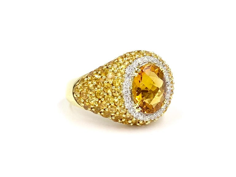 Fashionable 18 karat yellow gold wide ring featuring a 2.40 carat oval checkerboard faceted citrine surrounded by .28 carats of bright white diamonds and 2.75 carats of vivid yellow sapphires. Diamonds are approximately F color, VS2 clarity. Yellow