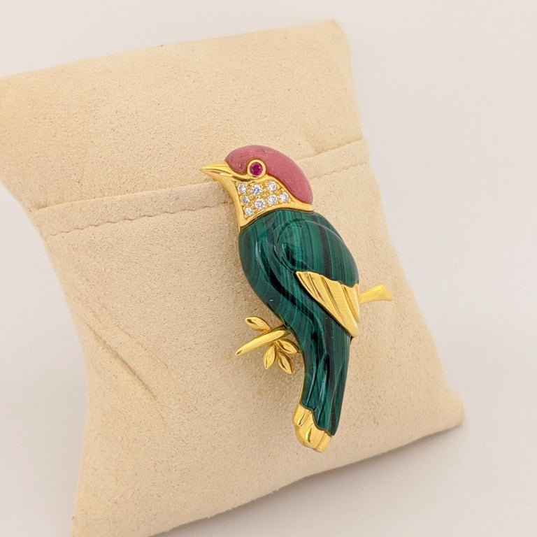 This lovely  18 Karat yellow gold Sparrow brooch is artfully crafted with carved Malachite , Pink Agate, and Diamonds. The sparrow has a ruby eye. The length of the brooch is 2