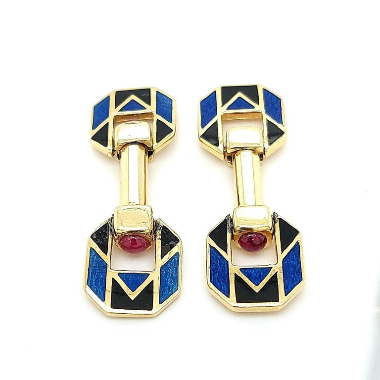 18 Kt Yellow Golden Blue & Black Enamel Cufflinks With Ruby stones   Stamped with MV,and you can see on the enamel the signs M and V as well.  I can t find which brand handcrafted those beautiful cufflinks ,but they re very nice.  Ruby: 4 round ruby