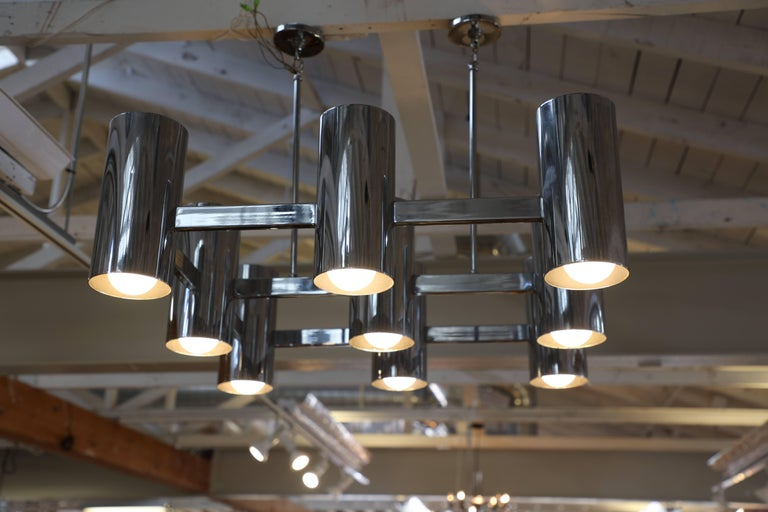 A nice chrome vintage fixture with nine heads and lights on top or bottom. They can be turned on together or separately. Attaches to the ceiling with two rods. Not sure of the manufacturer or designer but it unusual. It good age appropriate