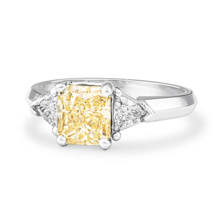 Captivating 3-stone diamond ring designed in 18K white gold that features one 1.80 carat total radiant diamond (Y-Z color, SI2 clarity) and 0.41 carats in two perfectly matched trillion diamonds. The ring was crafted in a size 7 and may be resized