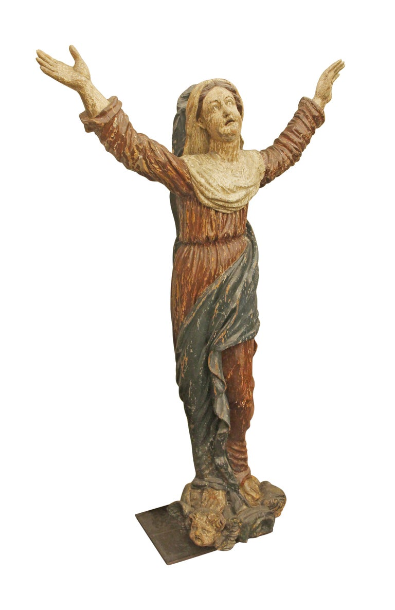 Saint statue made out of carved wood from Italy, circa 1800s. There are angel heads at the base of the figure. This can be seen at our 302 Bowery location in Manhattan.