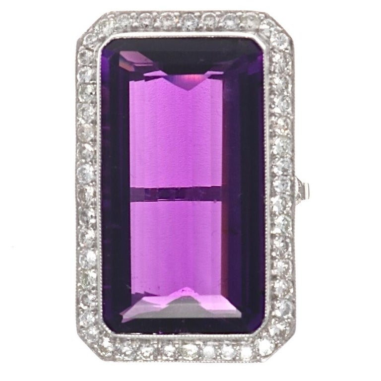 This natural richly colored elongated amethyst set in a halo diamond ring makes for a unique and striking presentation. Featuring a vivid 18.17 carat emerald cut purple amethyst and well matched white diamonds. Crafted in platinum. Ring size 5 3/4