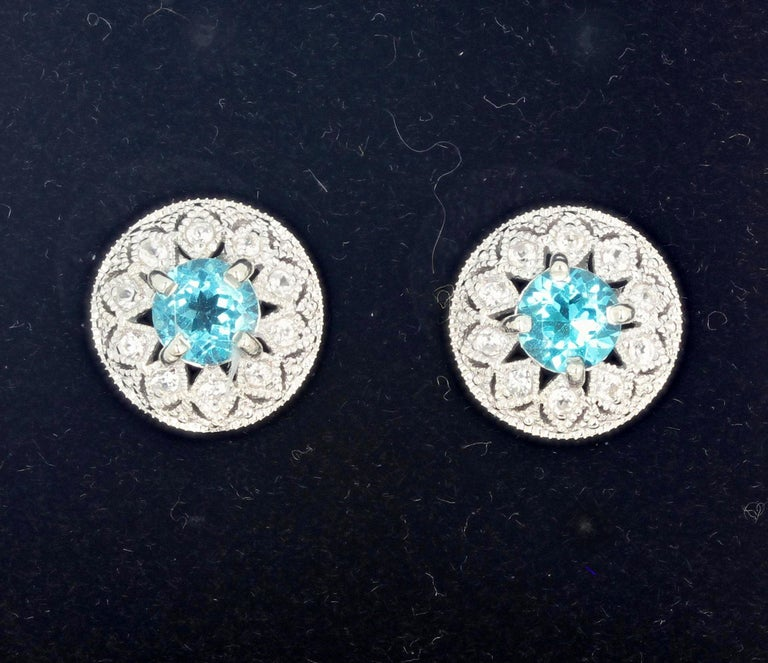 Brilliant blue round Topaz (6 mm) enhanced with teeny tiny little white Diamonds set in rhodium plated sterling silver stud earrings.  The earrings are approximately 13.5 mm.  More from this jeweler by putting gemjunky into your 1stDibs search bar.