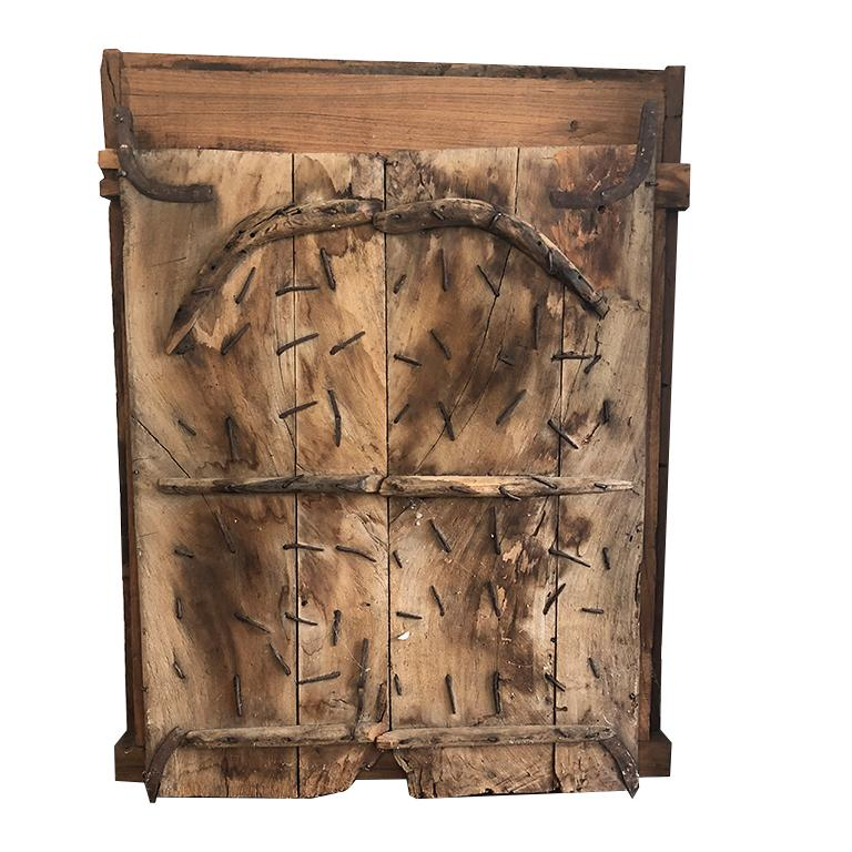 Hand-carved middle eastern window. Salvaged from a home in Iran in the 1800s. This piece was made to withstand armed intruders. Back has been secured shut with nails from that period. Front features a surround with intricate hand-carved reliefs with