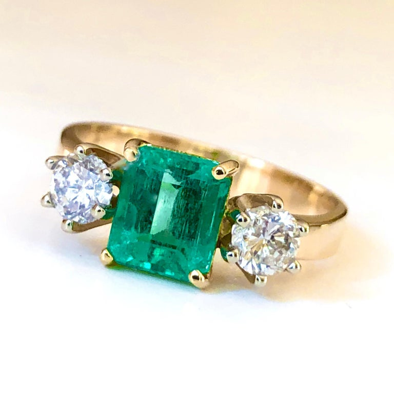 This elegant ring features a vivid AAA Colombian emerald 1.27 carat emerald cut, medium green color. Set in a 18K gold handmade, three-stone engagement ring with round brilliant cut diamonds side stones 0.56 ctw of H color and SI1 clarity, this ring