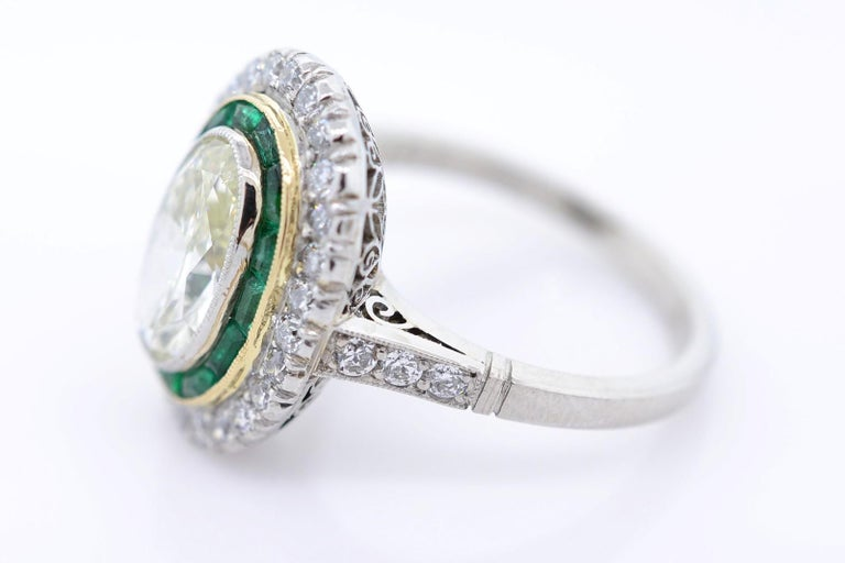 A stunning Art Deco recreation platinum ring.  The handmade setting flaunts a  Light Yellow 1.83 carat  Transitional oval cut diamond,  O/P color - SI1 clarity; measuring 7.00 x  4.70 mm.  Bezel set in 18KT yellow gold Fourteen calibrated Colombian