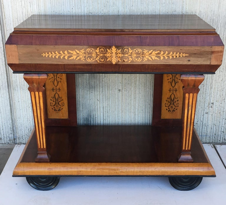 Early 19th century console in rosewood and maple. It features beautiful marquetry of rinceaux and floral motifs. It is resting on two straight legs in the back and two front columns legs. The console is set on a large base . Charles X period.