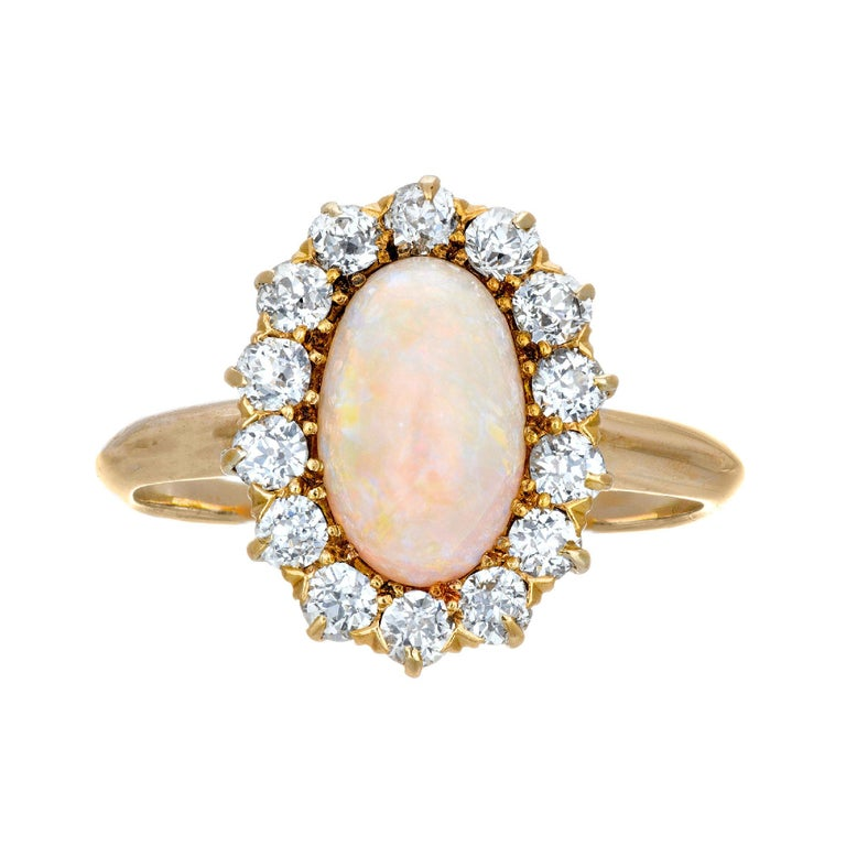 1.85cts Oval opal and diamond halo engagement ring.  circa 1900's with orange blue and green flash as well as some red, in a 14k yellow gold setting.   1 fine oval natural orange blue green Opal, approx. total weight 1.85cts, 9.8 x 4 x 3.8mm 14 old