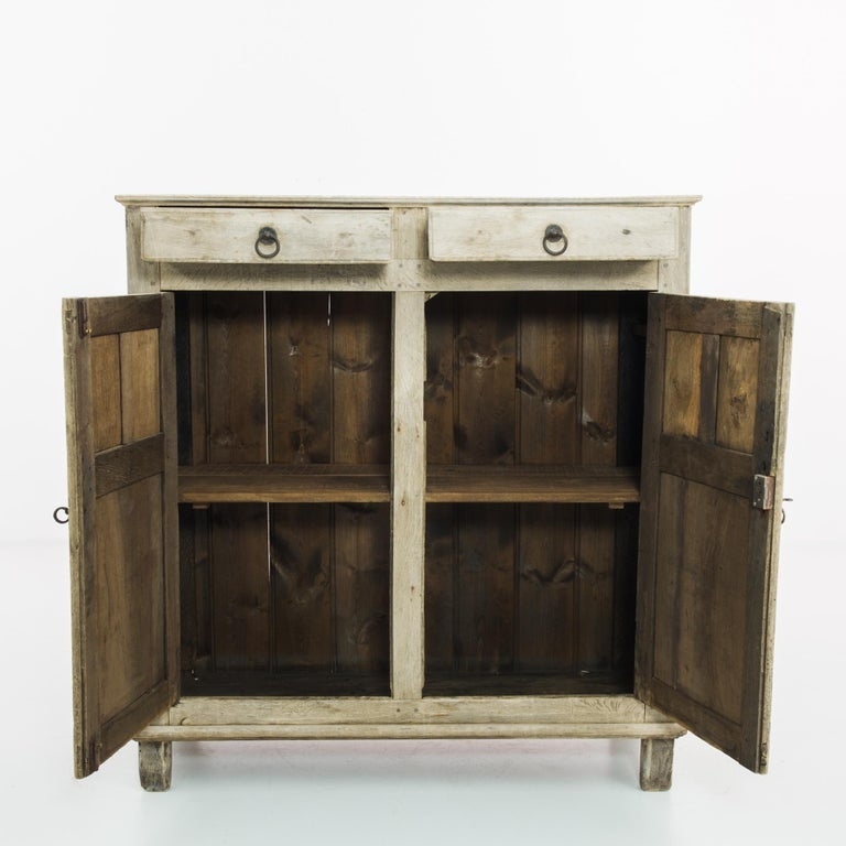 An oak buffet from 1860s Belgium. An upright frame, elevated upon square feet; panelling on the cupboard doors and cabinet adds a sober decorative touch. Door hinges, lock pieces and drawer handles in cast-iron lend a subtly gothic inflection,