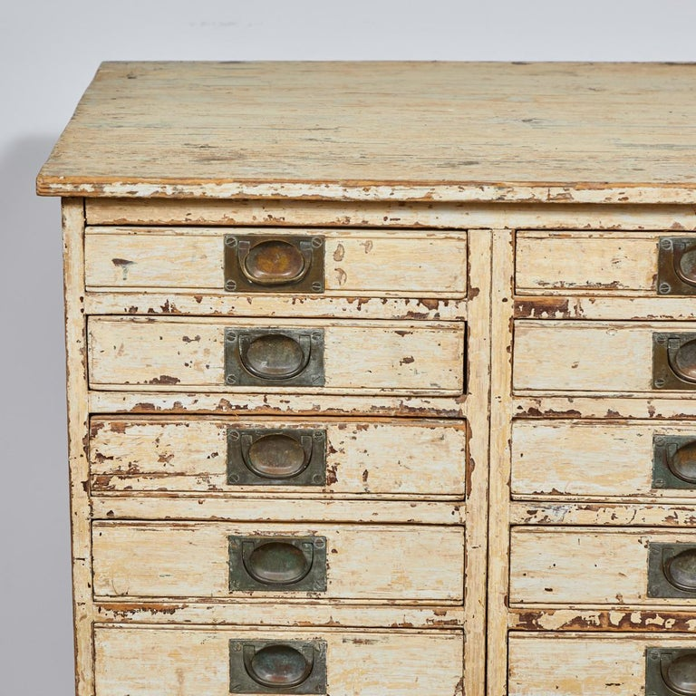 1860s English collector's drawer cabinet chest. 14-drawer painted plinth base chest with brass pulls. Serves as a multi-drawer cabinet, chest, or small sideboard.