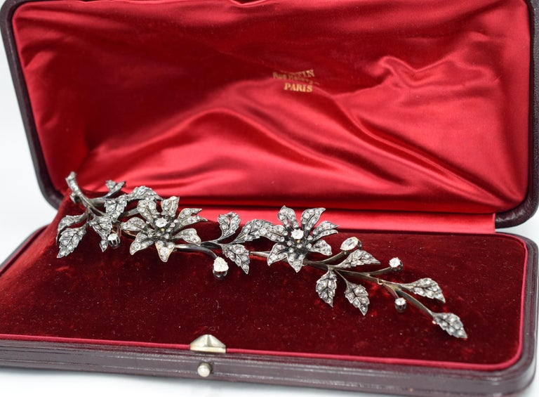Antique floral diamond brooch made in gold and silver. Circa 1860. The brooch consists of fourteen leaves and two flowers placed on a stem that is detatchable into five separate parts, the first and last part equipped with a pin. It is set with