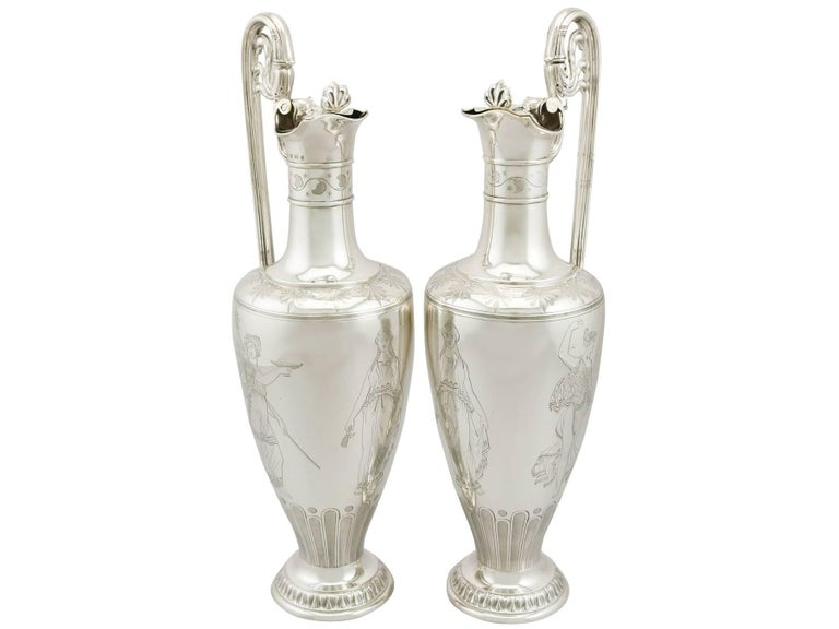 An exceptional, fine and impressive pair of antique Victorian English sterling silver claret jugs made by Elkington & Co; an addition to our Victorian silverware collection  These exceptional antique Victorian sterling silver jugs have a tapering