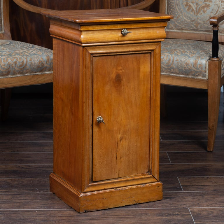 An Austrian Biedermeier style walnut bedside cabinet from the late 19th century, with single drawer, door and brass hand pulls. Born in Austria during the second half of the 19th century, this exquisite Biedermeier bedside cabinet features a