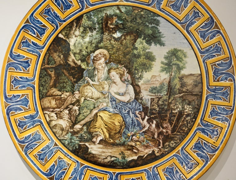 Late 19th century, very large earthenware ceramic sculpture platter or charger, of the French Second Empire period, entirely hand painted in Francois Boucher style, the romantic and subtly erotic scene as a central medallion depicts a young shepherd