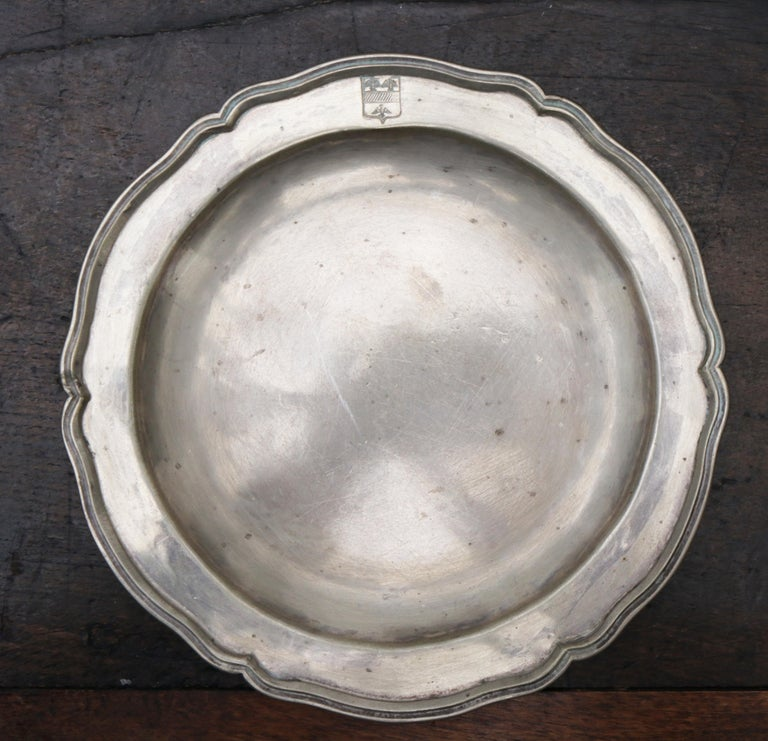 1875 set of eight 90% silver plates with shaped edges and engraved crest.   Silver by weight: 2310g.