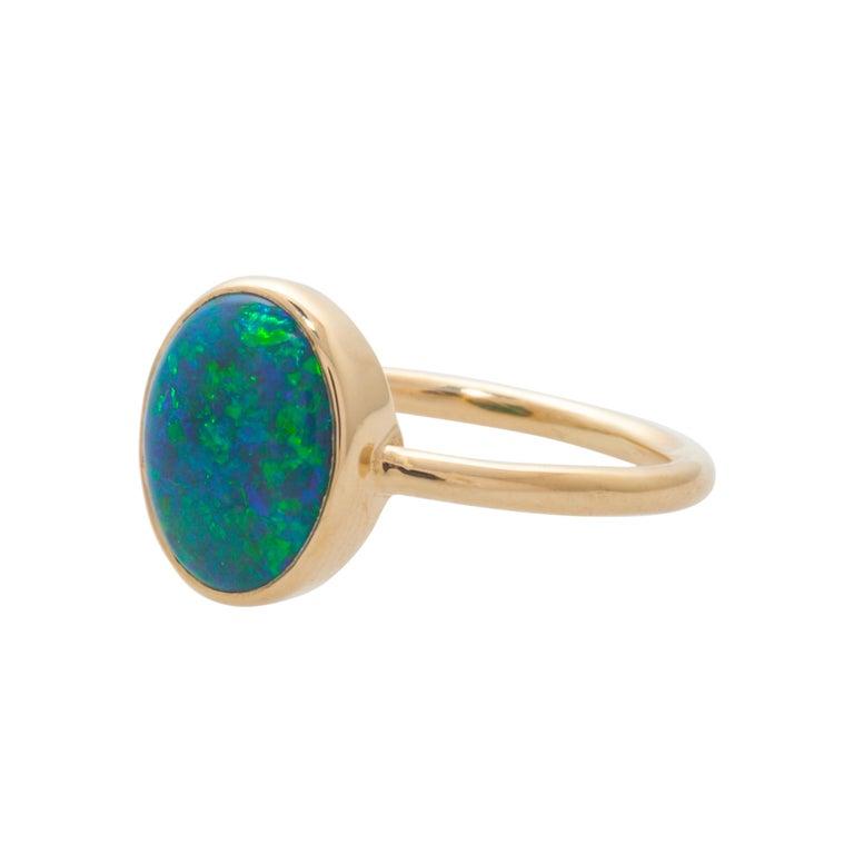 Bezel set Australian black opal weighs 1.88ct  Round wire shank measures 1.7mm  Set in 14k yellow gold