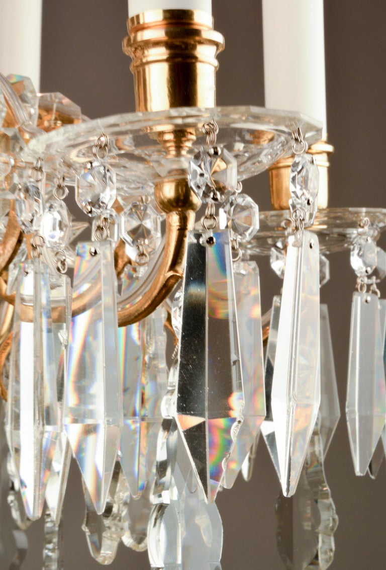This chandelier is a small example of the elegant fixtures Lobmeyr developed in the second half of the 19th century. It features tender arms of cast brass with warm antique gold finish. The arms are abundantly set with the typical hand-cut octagon