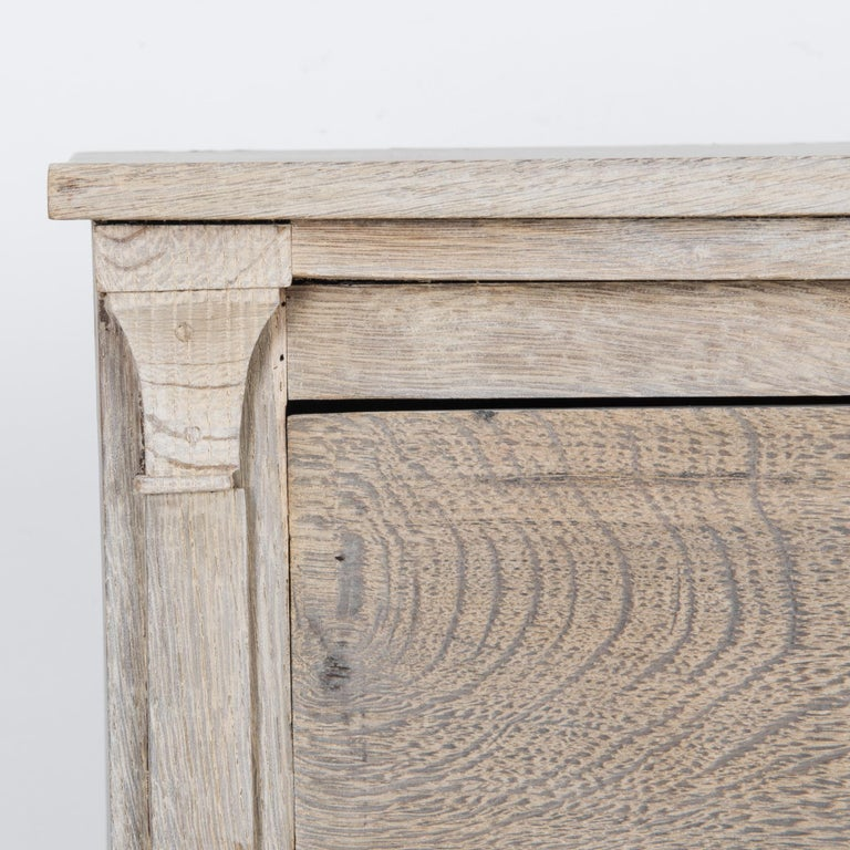 An antique oak chest of drawers from 1880s France. The upright form is enhanced by column moldings which unfold into graceful cornices, a subtle neoclassical accent. A liquid grain floats across the surface of the wood, restored to a pale natural