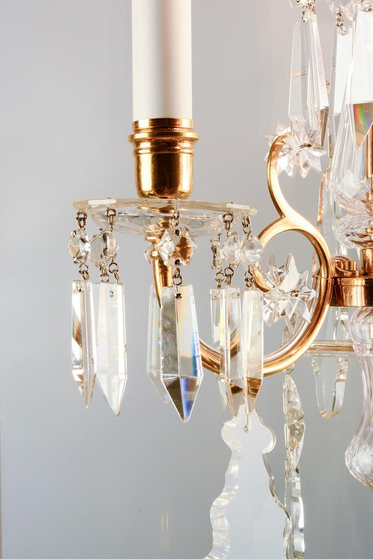 This style of wall sconce Lobmeyr developed in the second half of the 19th century. It features tender arms of cast brass with warm antique gold finish. The drop catchers are hung with finely cut crystal prisms. The parts of the slender central