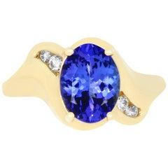 1.89 Carat Oval Shaped Tanzanite 0.11 Carat White Diamond Ring 14K Yellow Gold