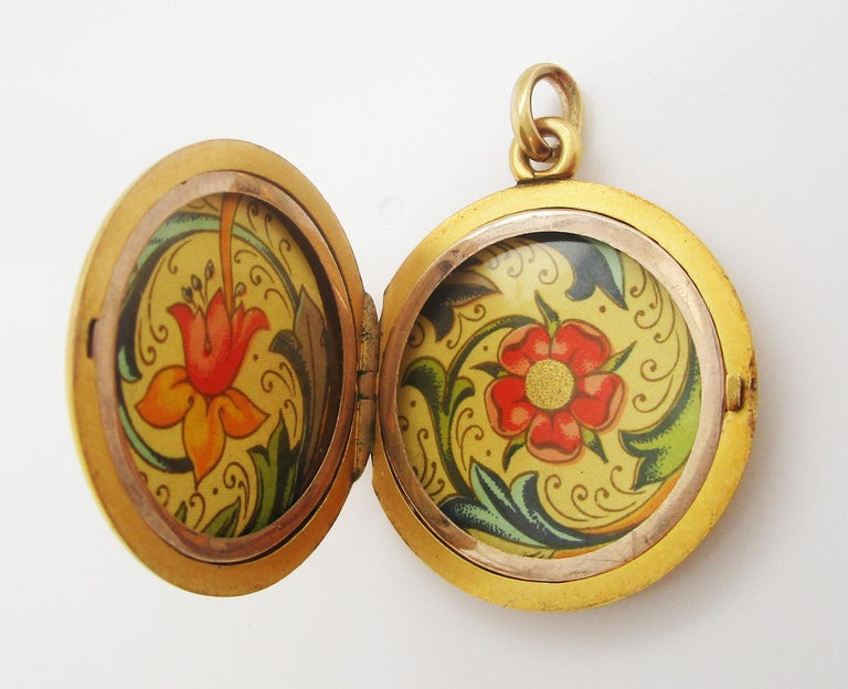 This is a gorgeous Victorian locket with a beautiful high-karat finish. The inside of the locket is decorated with a lovely floral paper. The back of the locket is open to be personalized! The locket is a classic round shape with a sleek, flat