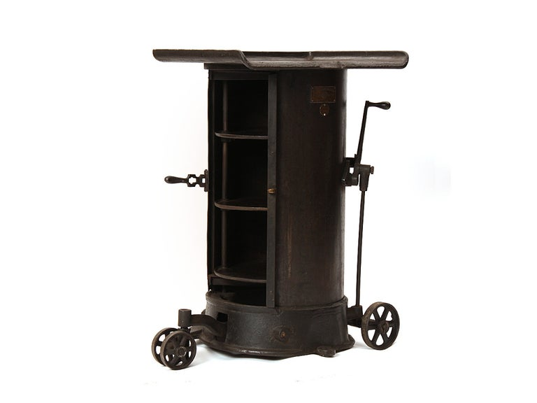 An Industrial cast iron rolling cabinet on three wheels with three concealed interior storage shelves. Retaining the original brass makers mark.